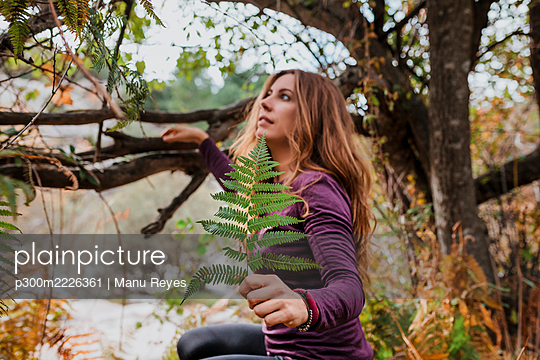 Woman holding leaf while standing by tree in forest at La Pedriza, Madrid, Spain - p300m2226361 by Manu Reyes