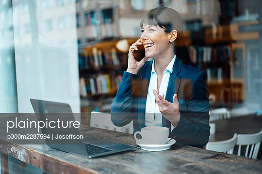 Mature female entrepreneur with laptop talking on mobile phone at cafe - p300m2287594 by Joseffson