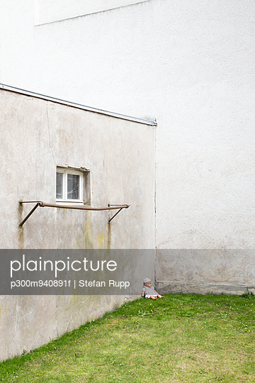 Germany, glum backyard with doll siiting on grass in a corner - p300m940891f by Stefan Rupp