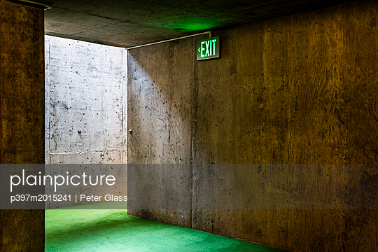 Notausgang in einem Gebäude aus Beton mit grünem Teppichboden - p397m2015241 von Peter Glass