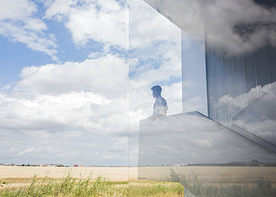 Pensive businessman on modern landing looking out window at sunny blue sky and clouds - p1023m1519836 by Martin Barraud