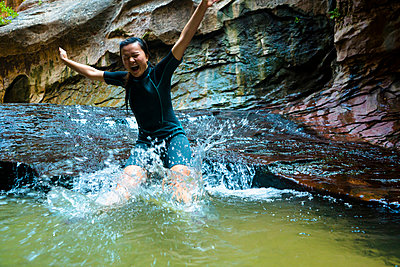 Cheerful woman jumping in pond by rock formation - p1166m1194043 by Cavan Images