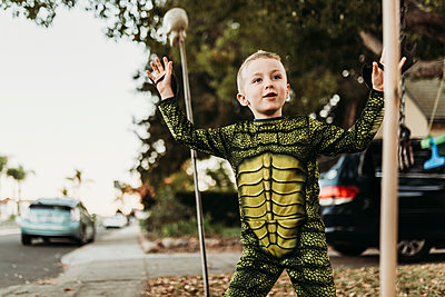 Young boy dressed as sea monster playing in costume at Halloween - p1166m2208404 by Cavan Images