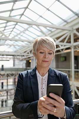 Businesswoman using smart phone in office atrium - p1192m2093747 by Hero Images