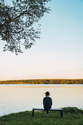 Young man sitting on a bench, looking at the lake - p300m2060767 by Kike Arnaiz