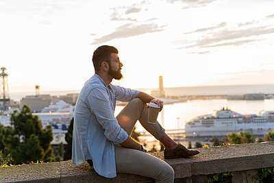 Man sitting on a wall on lookout above the city with view to the port, Barcelona, Spain - p300m2155154 by VITTA GALLERY