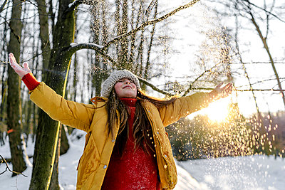 Girl in warm clothing standing with eyes closed under tree during snowfall - p300m2267072 by Oxana Guryanova