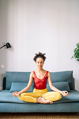 Young woman practicing lotus position on sofa at home - p300m2277283 by COROIMAGE