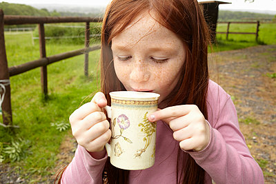 Girl drinking cocoa outdoors - p429m1450600 by Emma Kim