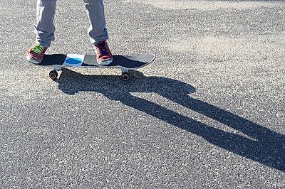 Detail of legs riding skateboard - p924m862100f by Karen Fox