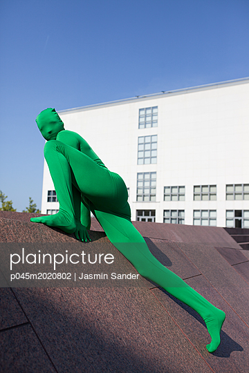 Mann im Morpshuit klettert Mauer hoch - p045m2020802 von Jasmin Sander