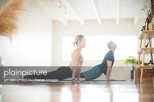 A couple in upward facing dog position during yoga. - p1166m2192074 by Cavan Images
