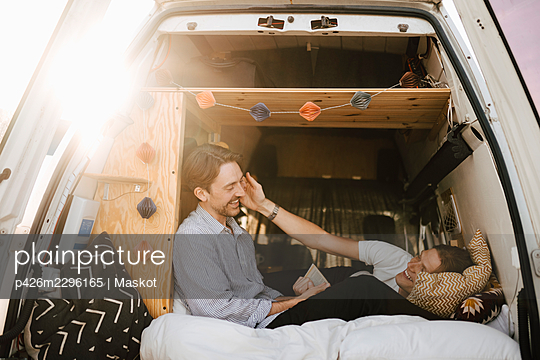 Happy gay couple spending leisure time in camping van during vacation - p426m2296165 by Maskot