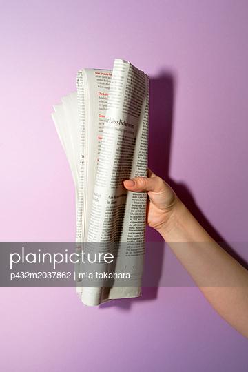 Frauenhand hält Tageszeitung - p432m2037862 von mia takahara