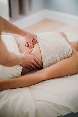 A massage therapist applies pressure to the back of a female client - p1166m2107021 by Cavan Images