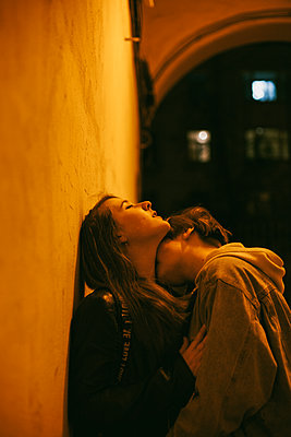 Woman kissing girlfriend in city during night - p1166m2111669 by Cavan Images