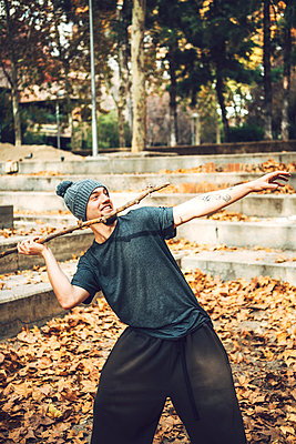 Smiling man in knit hat throwing stick in park during autumn - p300m2206685 by klublu