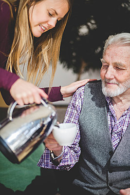 Young woman pouring drink in cup being held by grandfather in nursing home - p426m2018659 by Maskot