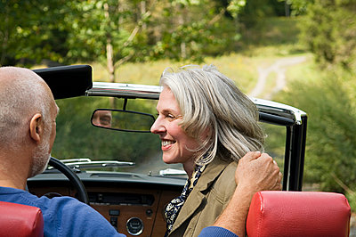 Rear view of older couple driving convertible - p555m1411198 by Alberto Guglielmi