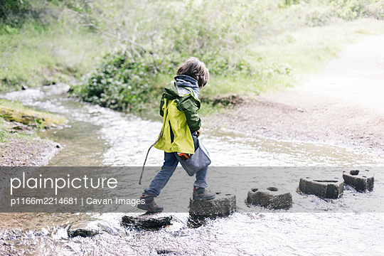 Side view child walking through stones by river - p1166m2214681 by Cavan Images