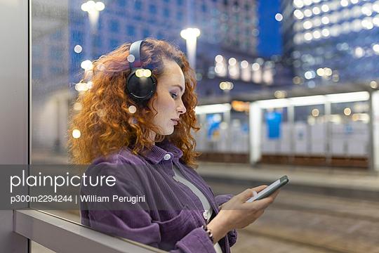 Woman wearing headphones using smart phone seen through glass at tram station - p300m2294244 by William Perugini
