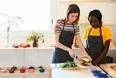 Friends preparing pineapple in kitchen - p300m1587750 von Bonninstudio