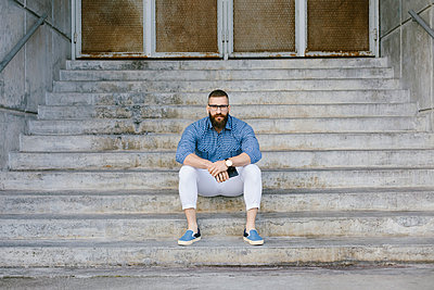 Portrait of bearded hipster businessman with smartphone sitting on stairs - p300m2060026 by Nando Martinez