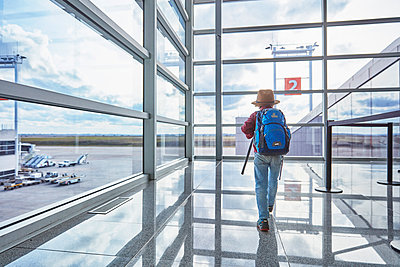 Boy with backpack at the airport running towards departure gate - p300m2070855 by Stefan Schütz
