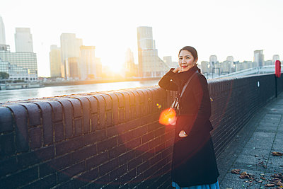 UK, England, London, Mid adult woman leaning against wall on riverbank in Rotherhithe - p352m1349962 by Karin Enge Vivar