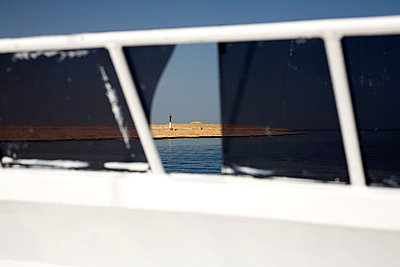 Lighthouse seen through boat window - p3881731 by Ulrike Leyens
