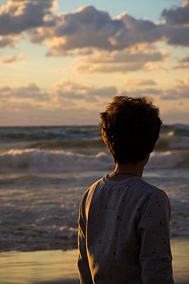 Silhouette of a boy standing on the beach at sunset  - p794m1510979 by Mohamad Itani