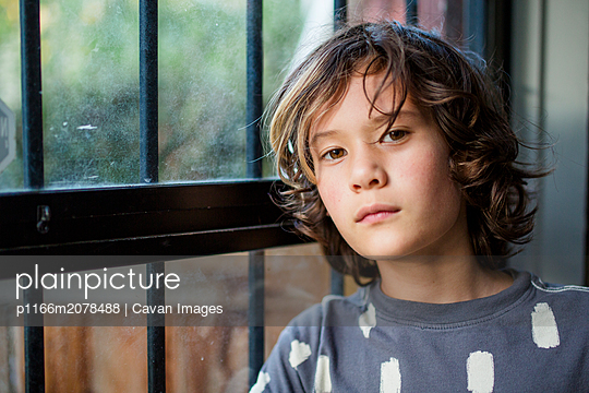 a serious boy looks directly at the camera in an open doorway - p1166m2078488 by Cavan Images