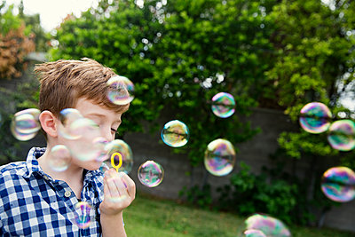 Boy blowing bubbles in yard - p1166m1150480 by Cavan Images