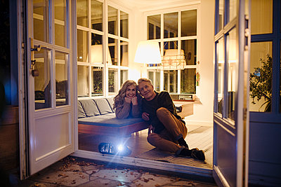 Senior couple watching a movie with a video projector at home at night - p300m2155266 by Gustafsson