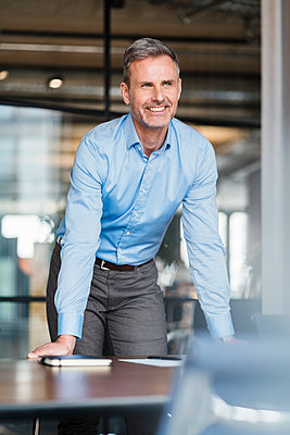 Smiling businessman day dreaming while leaning on table at office - p300m2273943 by Daniel Ingold