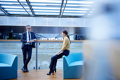 Businessman and woman having discussion in office atrium - p429m1417643 by Jakob Helbig