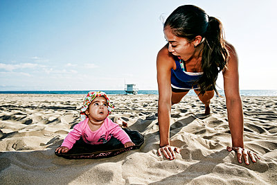 Mother and daughter doing push-ups at beach - p555m1305533 by Peathegee Inc