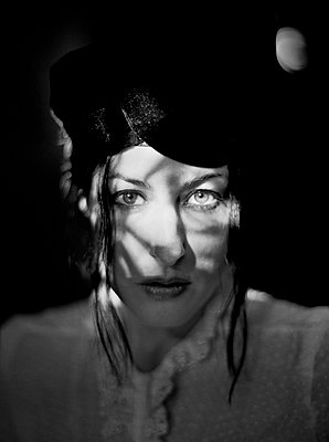 Head and Shoulders Portrait of Serious Mid-Adult Woman with Shadows on Face - p694m1493398 by Jason Langer
