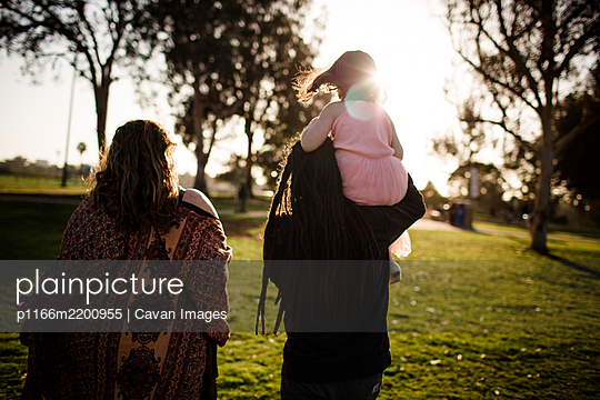 Niece on uncle's shoulders walking with aunt and sunset - p1166m2200955 by Cavan Images