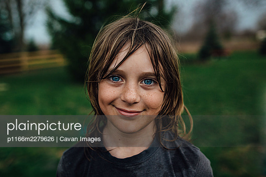 young boy looking at camera with smirk - p1166m2279626 by Cavan Images