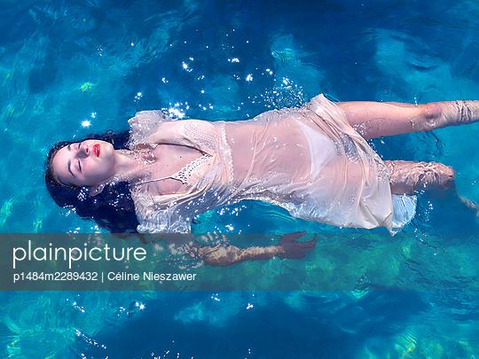 Woman wearing dress in pool - p1484m2289432 by Céline Nieszawer