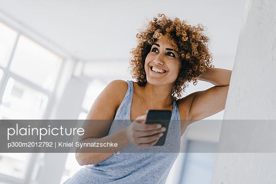Laughing woman using smartphone - p300m2012792 von Kniel Synnatzschke