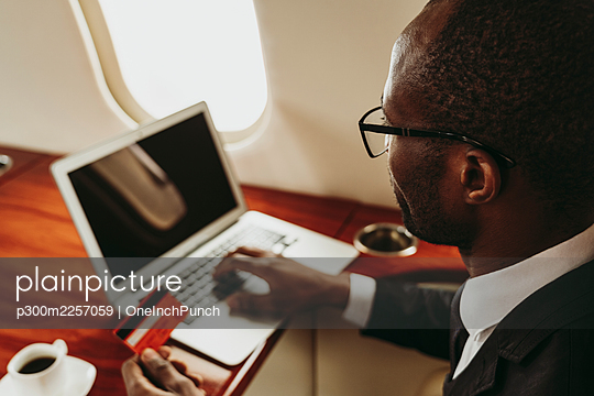 Businessman doing online payment through laptop in airplane - p300m2257059 by OneInchPunch