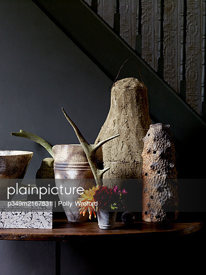 Earthenware pots and cut flowers on hall table - p349m2167831 by Polly Wreford
