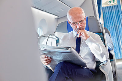 Businessman reading newspaper on airplane - p1023m1519955 by Rafal Rodzoch