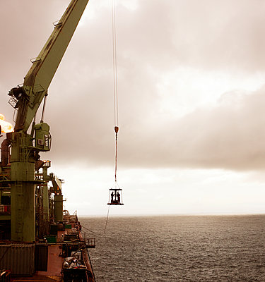 Workers on platform hanging by crane over sea - p1166m1176421 by Cavan Images