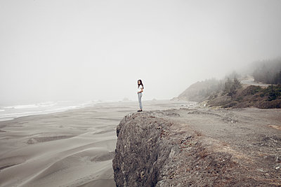 Side view of woman standing on cliff at beach during foggy weather - p1166m1210488 by Cavan Images