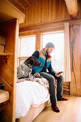 Man with dog using smart phone on cabin bed - p1192m2093920 by Hero Images