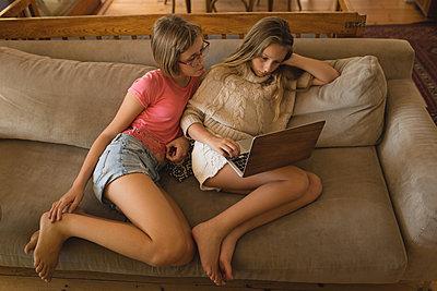 Siblings using laptop in living room - p1315m1579151 by Wavebreak