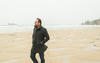 France, Bretagne, Finistere, Crozon peninsula, man walking on the beach - p300m1127599f by Uwe Umstätter